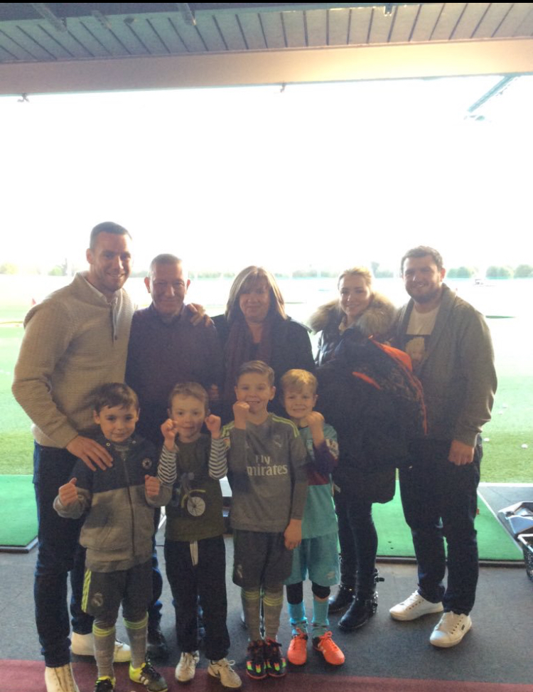 adults-and-young-children-smiling-together-at-Topgolf