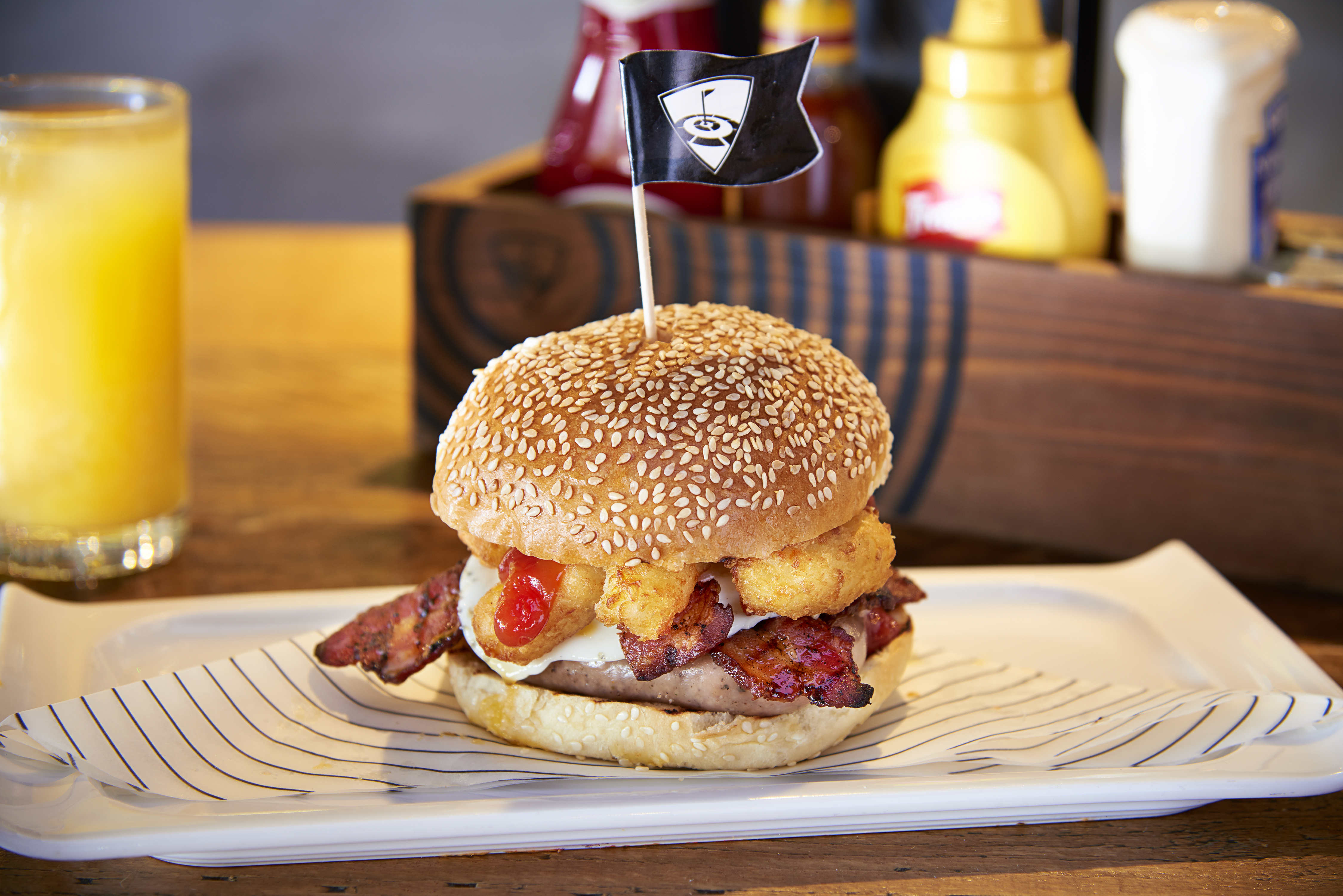 Topgolf breakfast bap with sausages. hash browns, bacon and an egg