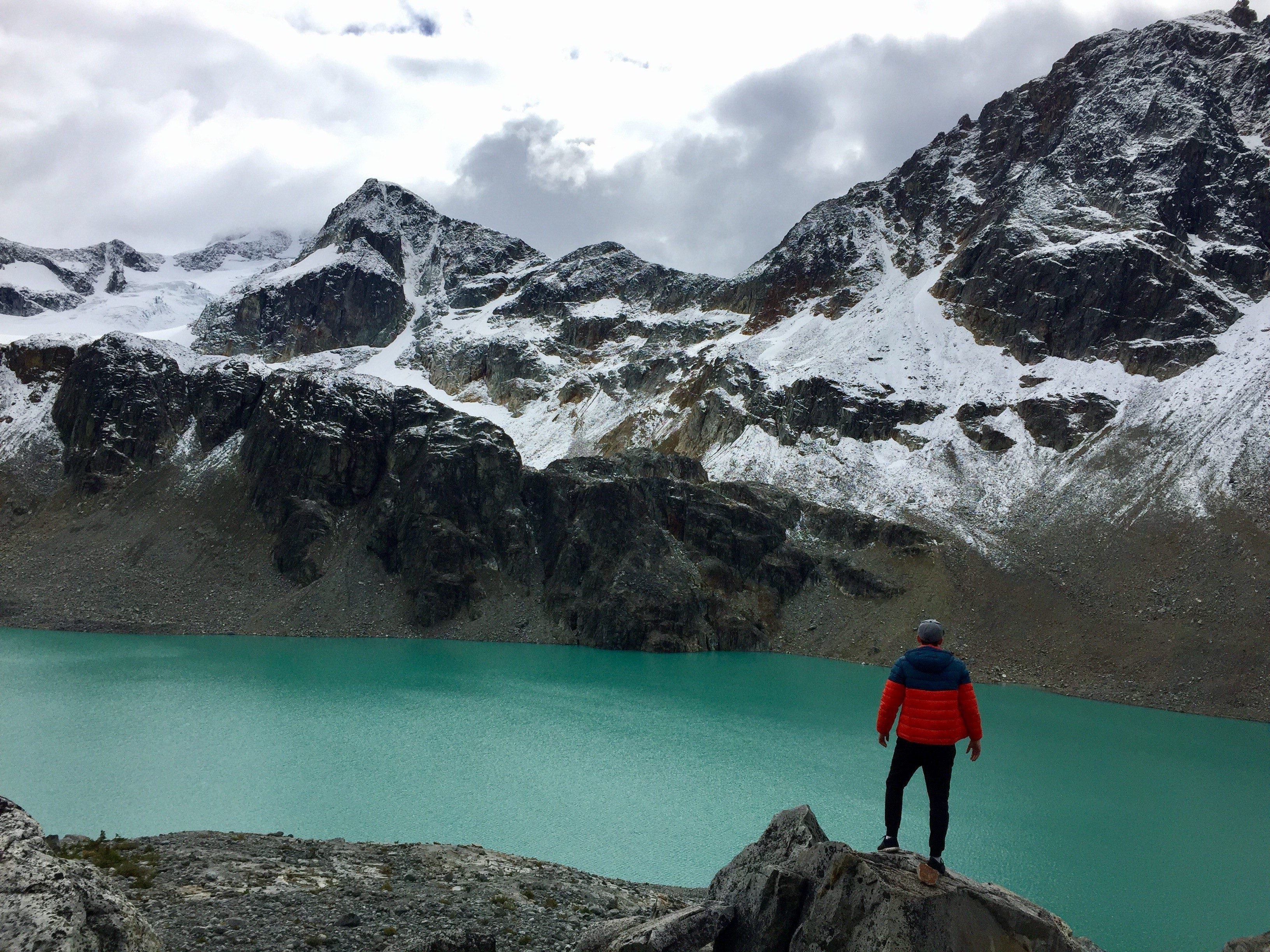 An explorer standing in front of water and a mountain