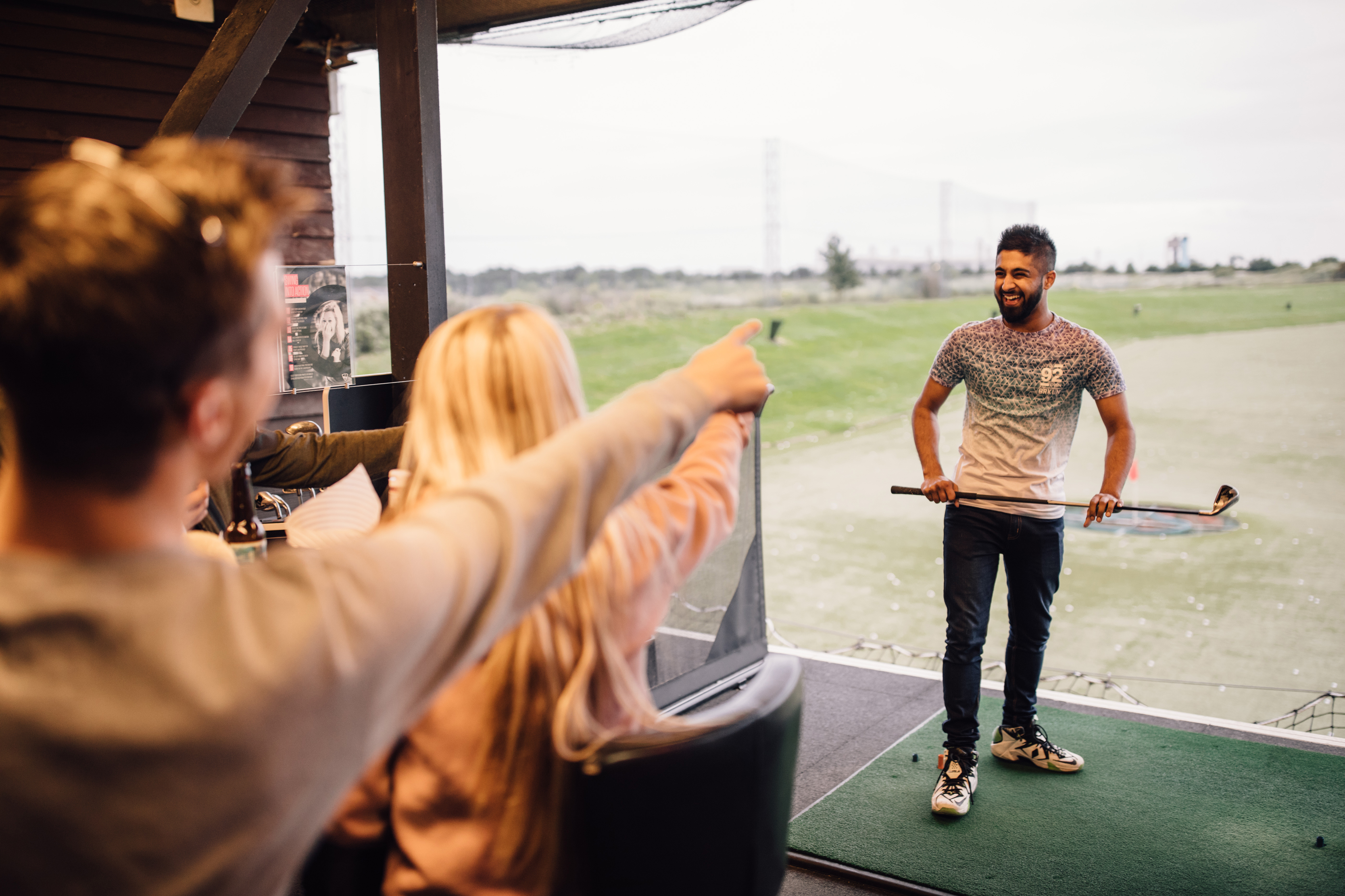 friends laughing at Topgolf